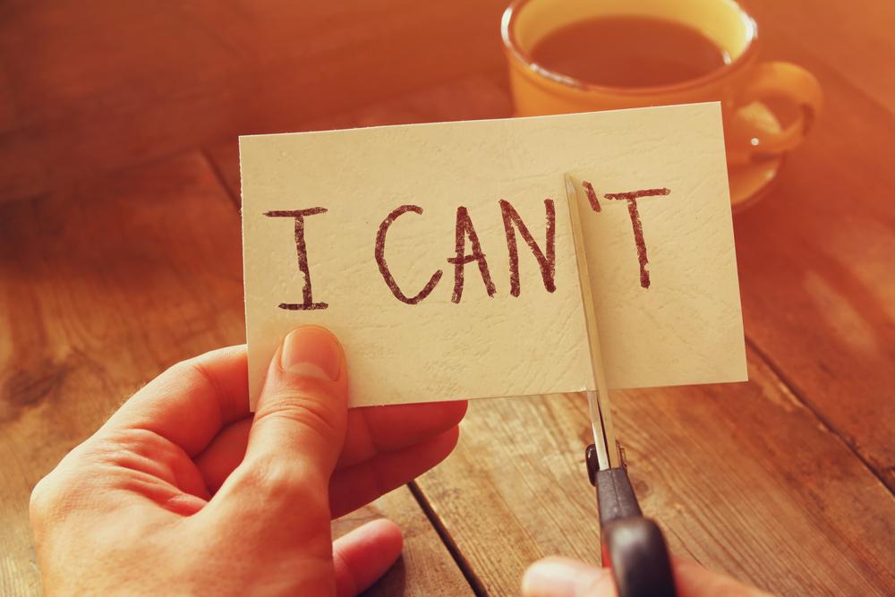 「I CAN'T」と書かれたカードの「N'T」の部分をハサミで切り取る人の手元