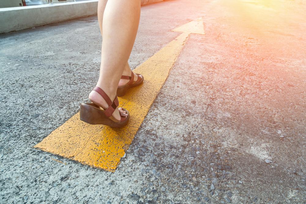 道に書かれた真っ直ぐな矢印に向かって歩く、サンダルを履いた女性