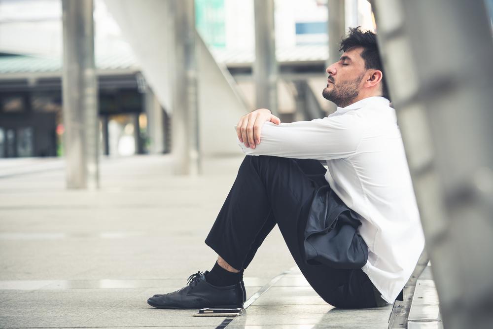 街中で膝を抱えて座り込み空を仰ぐ男性