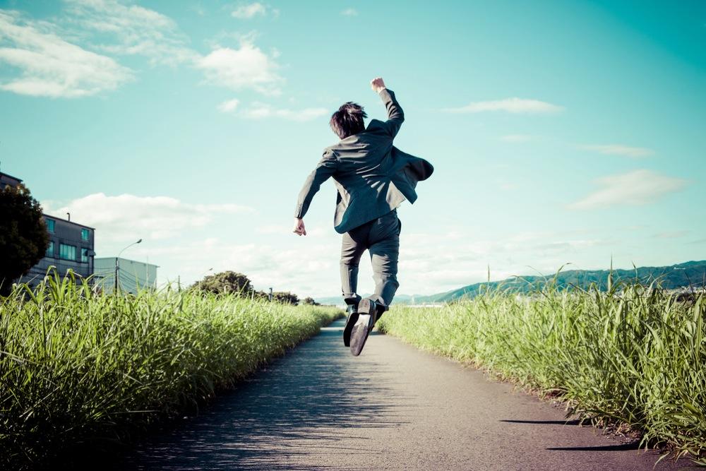 ガッツポーズをして飛び上がる、喜んだ様子のスーツを着た男性