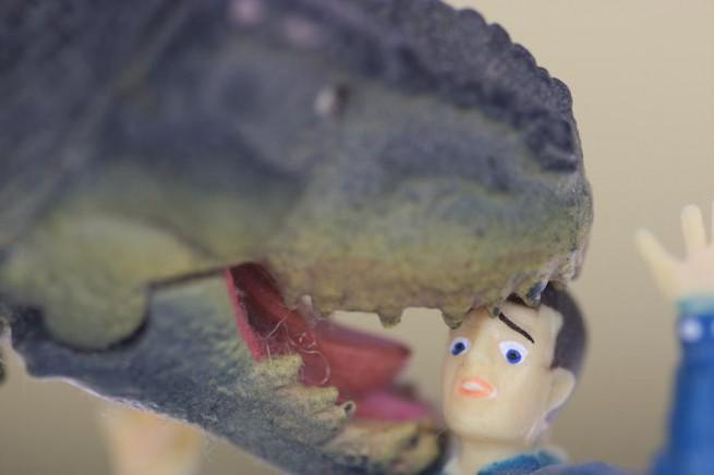 恐竜のフィギュアに頭を噛まれる男性の人形