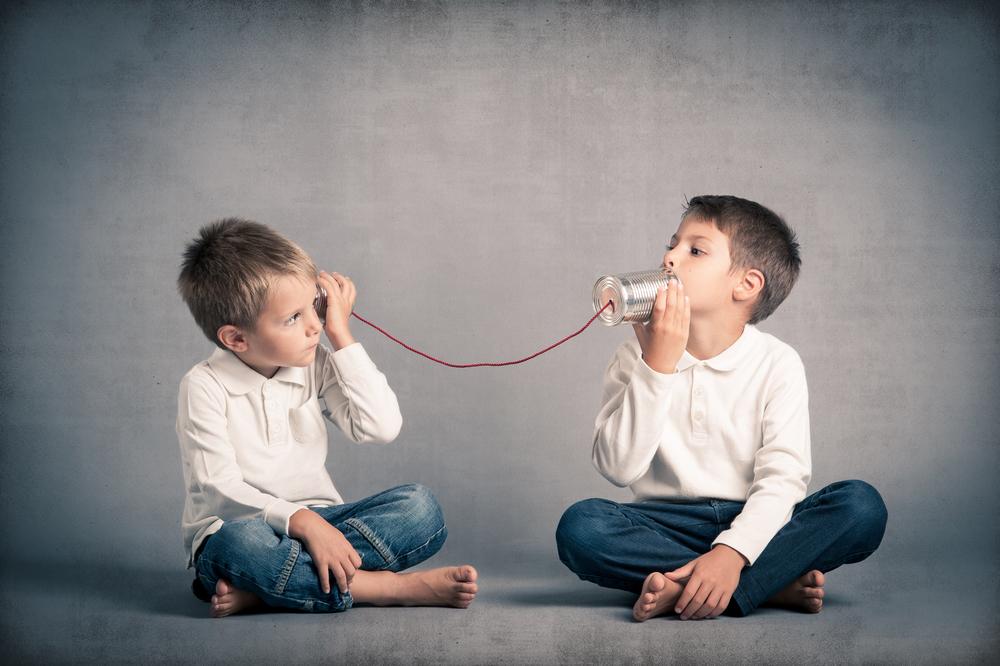 糸電話で話をする少年達