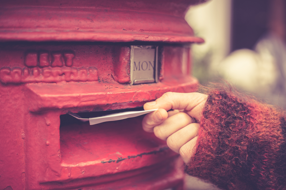 ポストに手紙を出す人の手元