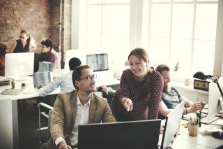 パソコンのモニターを見ながら仕事の会話をする男女