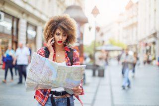 街中で地図を広げ困った表情で電話をする女性