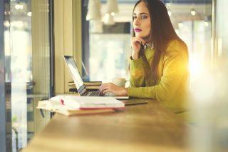 ノートパソコンを開きながら考え事をする女性