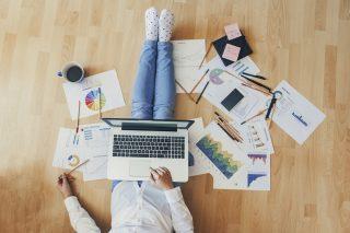 プリントアウトしたグラフや色鉛筆の散らばった床に座り、ノートパソコンを操作する女性