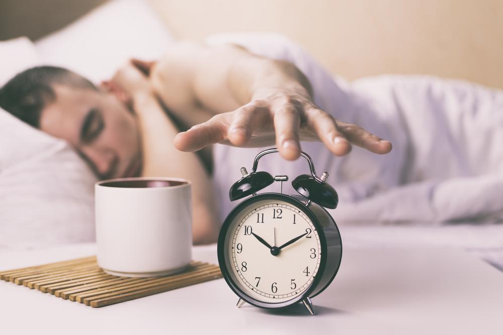 枕元の目ざまし時計を消そうとする男性