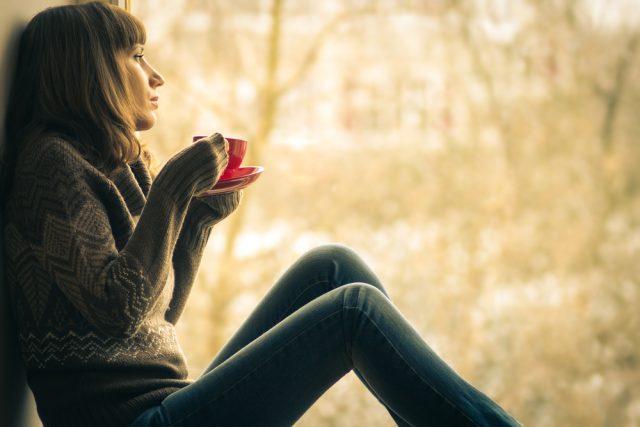 窓辺に座ってホットドリンクをのむセータを着た女性