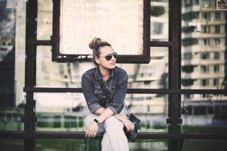 足を組んでベンチに腰掛けるサングラスをかけた女性