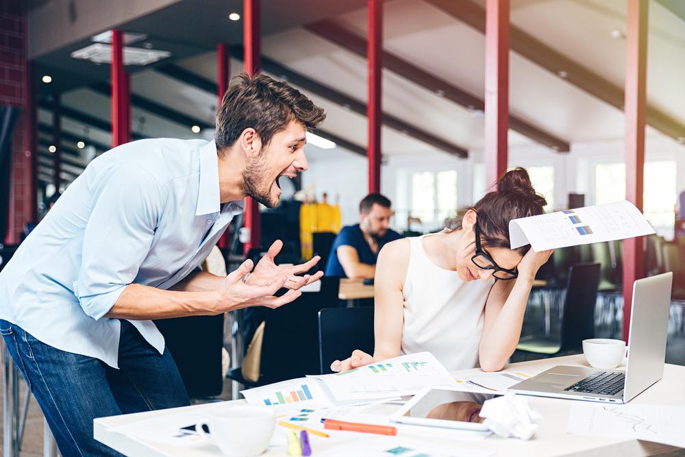 職場で叱責する男性と頭を抱える女性