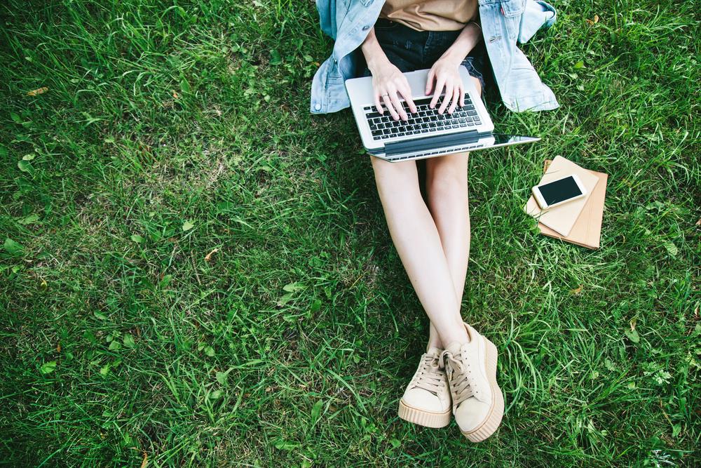 原っぱに座ってノートパソコンを操作するラフな格好の女性