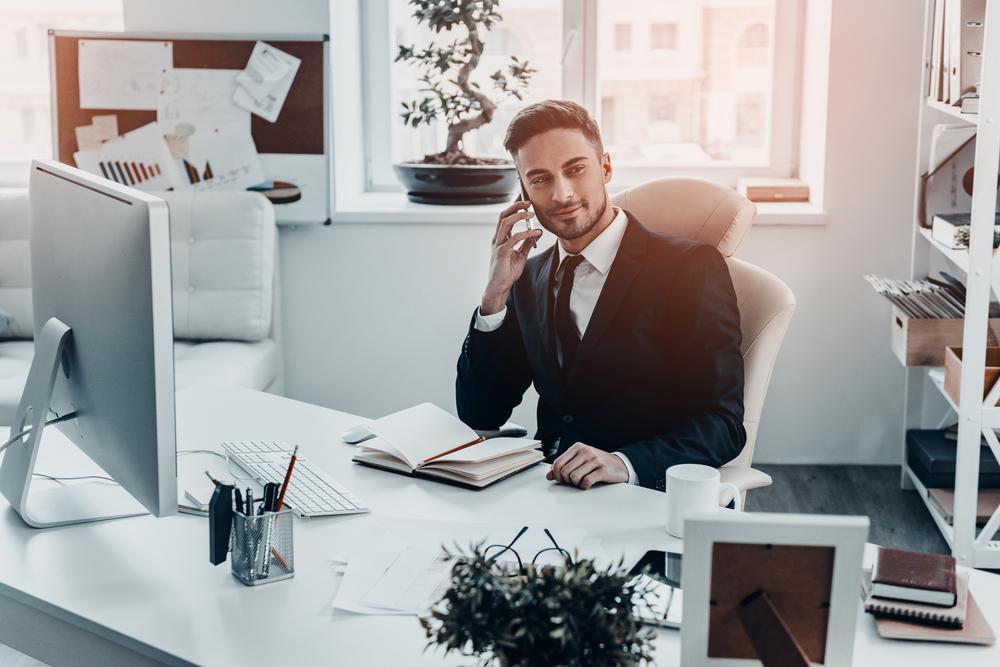 オフィスの椅子に座り、笑顔で電話を取るスーツ姿の男性