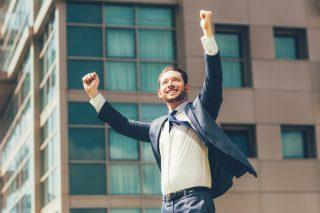 笑顔でガッツポーズをするスーツ姿の男性