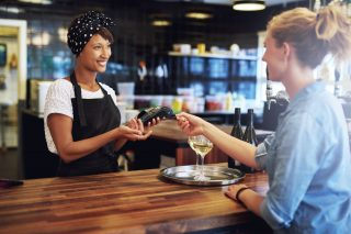 飲食店で働く女性と支払いをする女性
