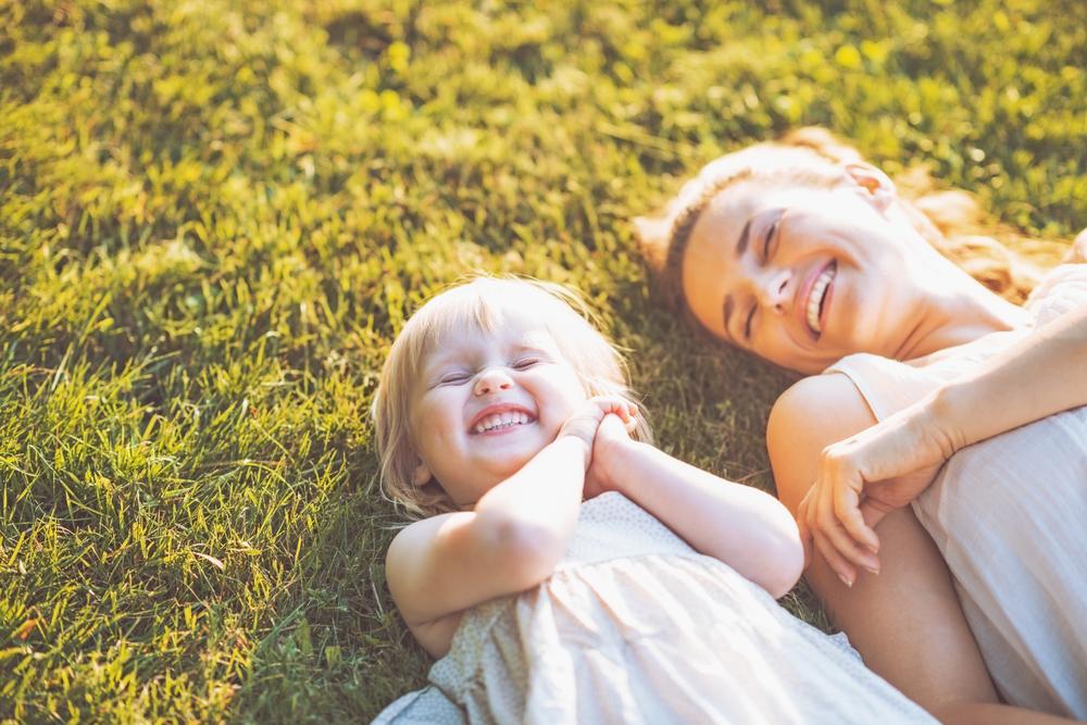 芝生の上に寝転ぶ笑顔の親子