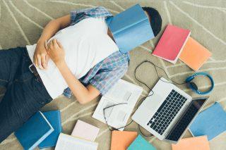 本を顔に乗せて居眠りする男性