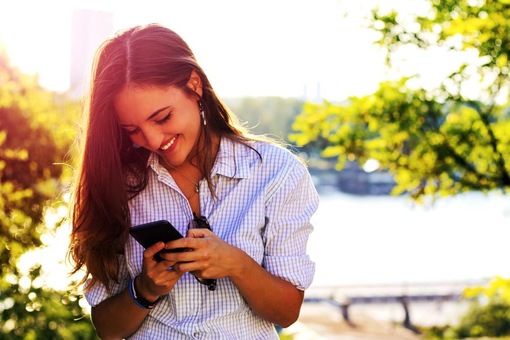スマートフォンを見て喜ぶ女性