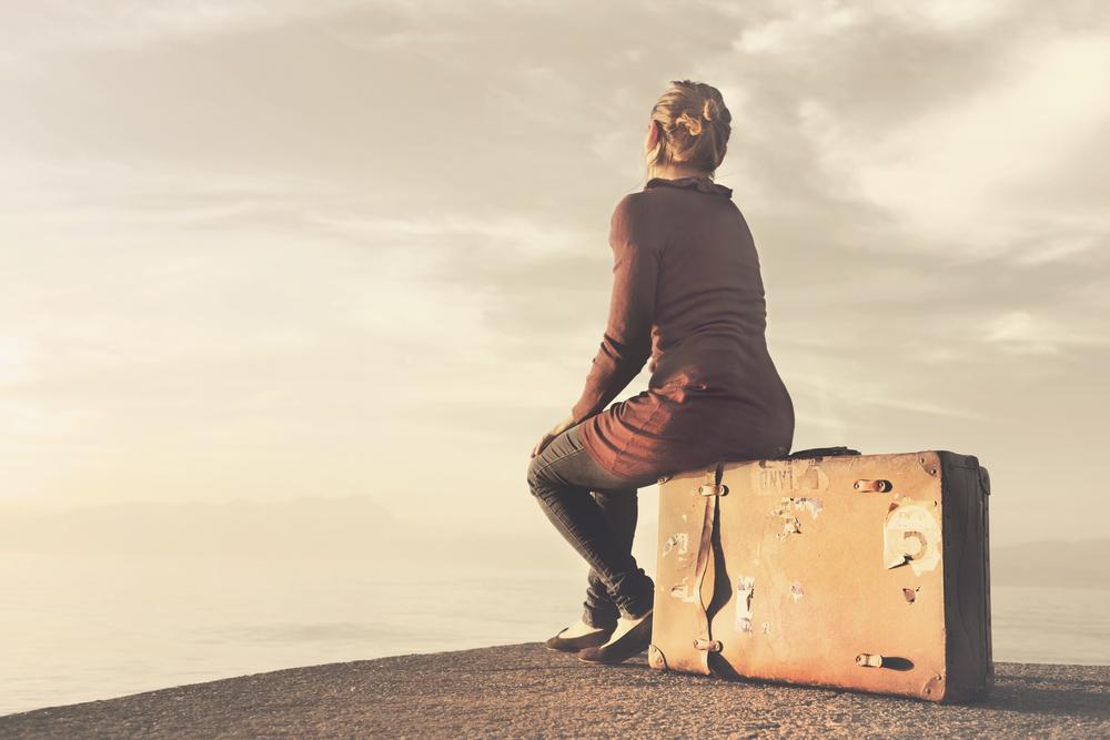 ボロボロのトランクに腰掛け、遠くを見つめる女性