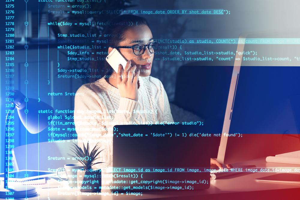 スマートフォンで会話する女性とプログラミング画面