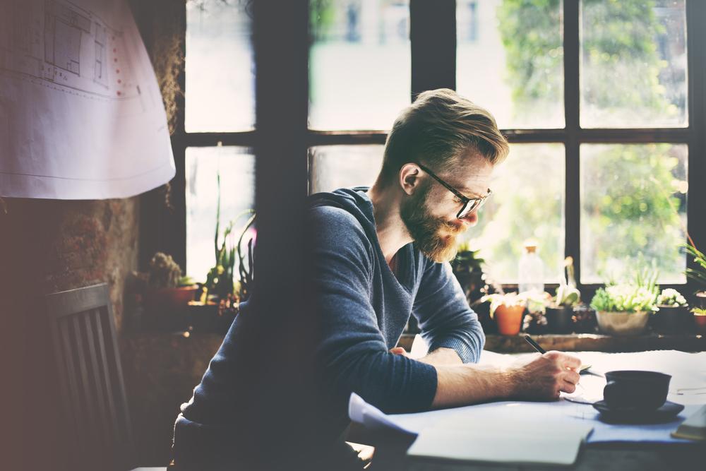 窓辺に座り設計図を書く男性