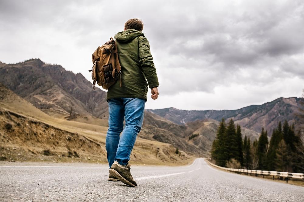 荒れた山に入っていく道を歩いている男性