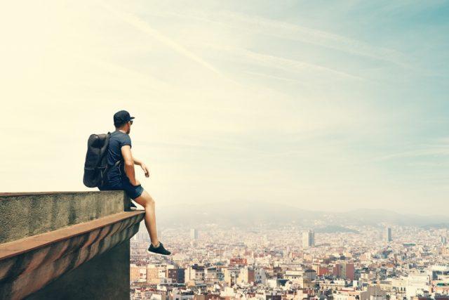 建物の角に腰をかけ、町を見下ろすリュックを背負った男性