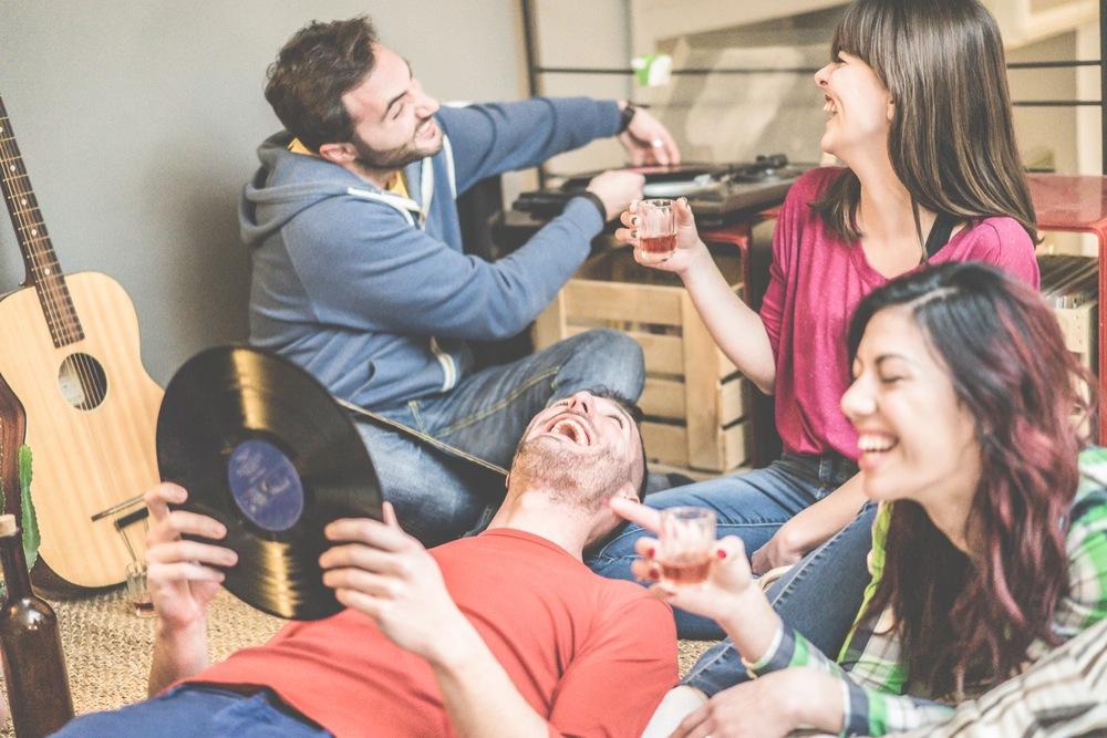 レコードをかけながら狭い部屋で飲み会をする若い男女のグループ