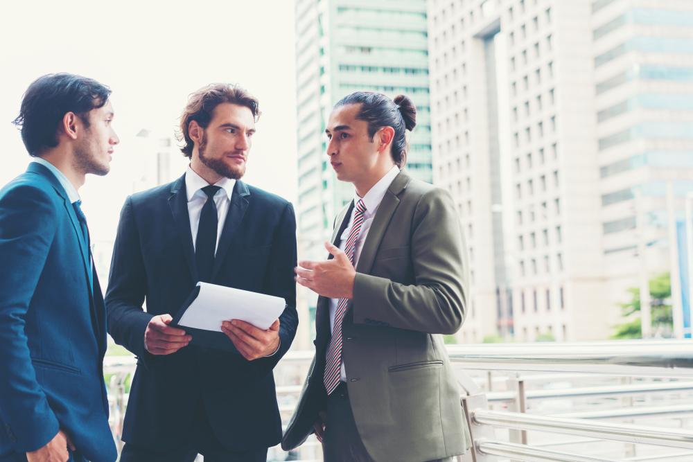 ビジネス街で話し合うスーツの男性達