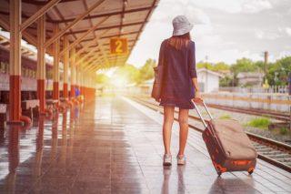 プラットホームに立つ、スーツケースを持つ女性