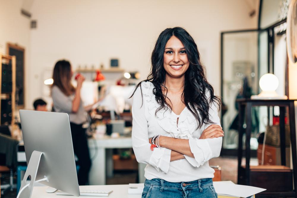 腕を組んでオフィスの机の前に立つ笑顔の女性