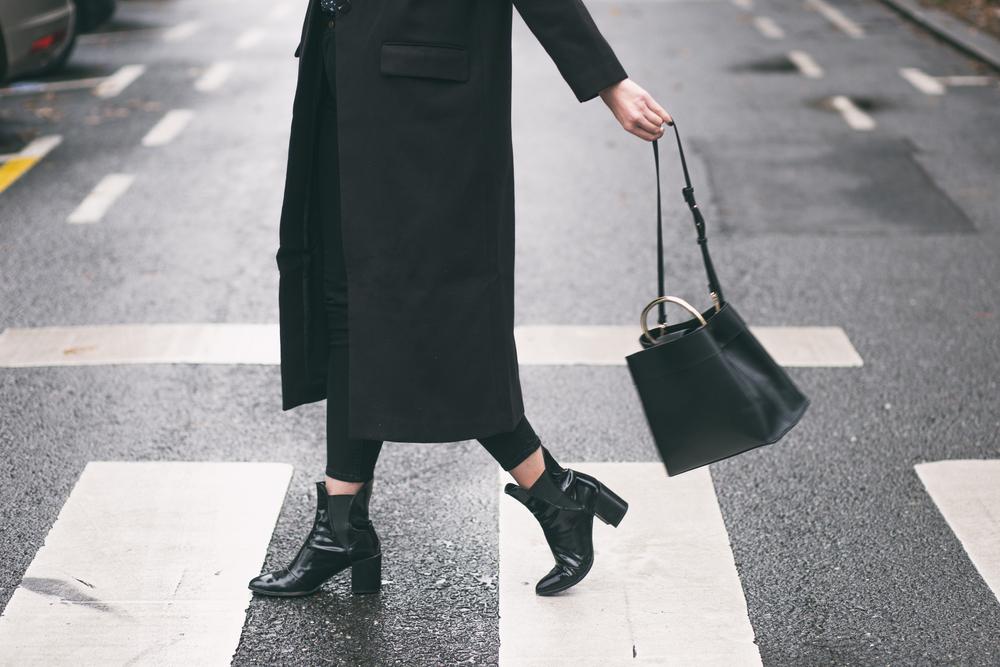 横断歩道を歩く黒いスカートの女性