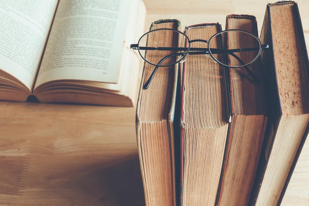 数冊の古い本と、その本の上に置かれたメガネ