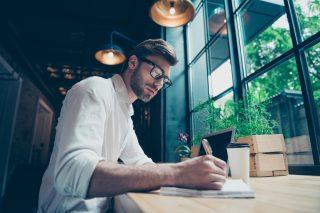 カフェでノートに何か書き留めるメガネをかけた男性