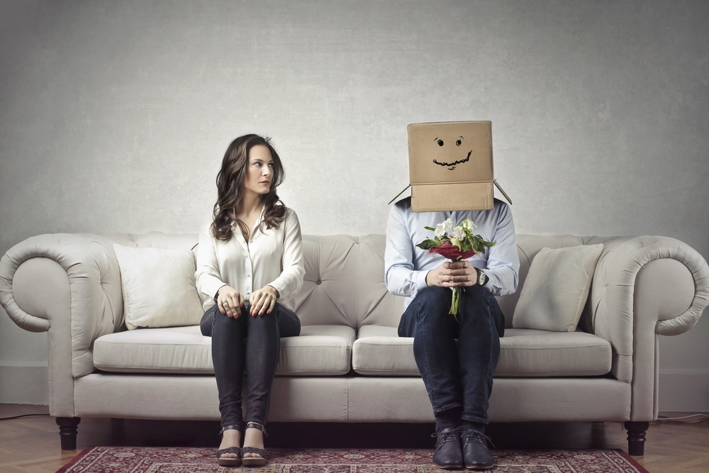 頭をダンボール箱で覆った恥ずかしがり屋の男性と、隣に座って彼を見る女性