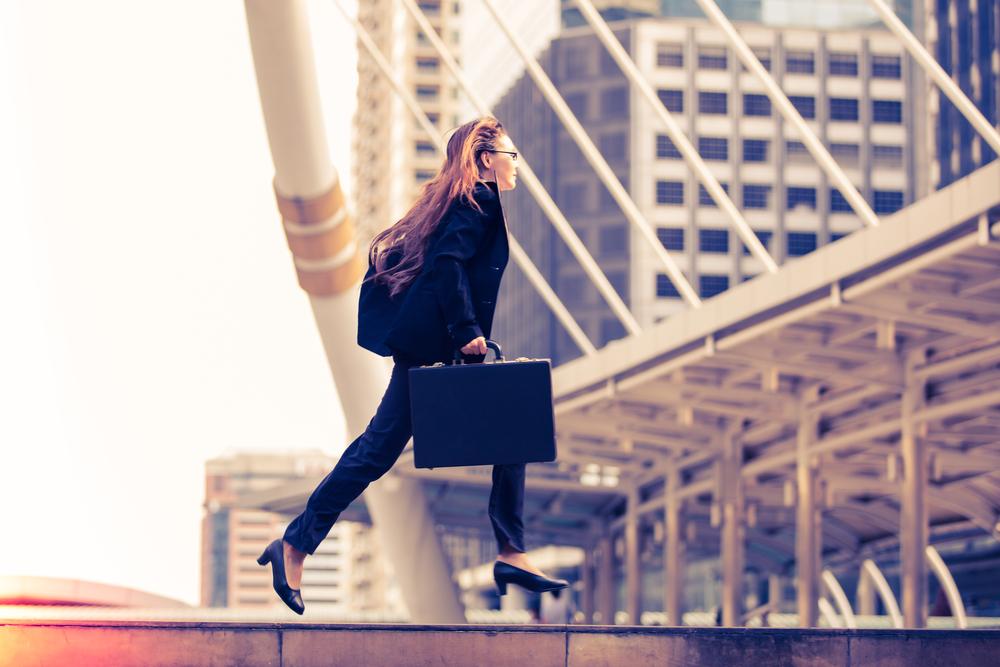 ハイヒールを履いて大きなカバンを持ち、颯爽と走る女性