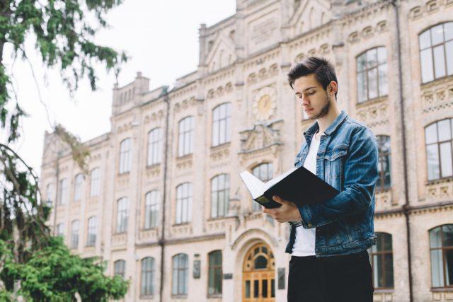 分厚い本を読む若い男性