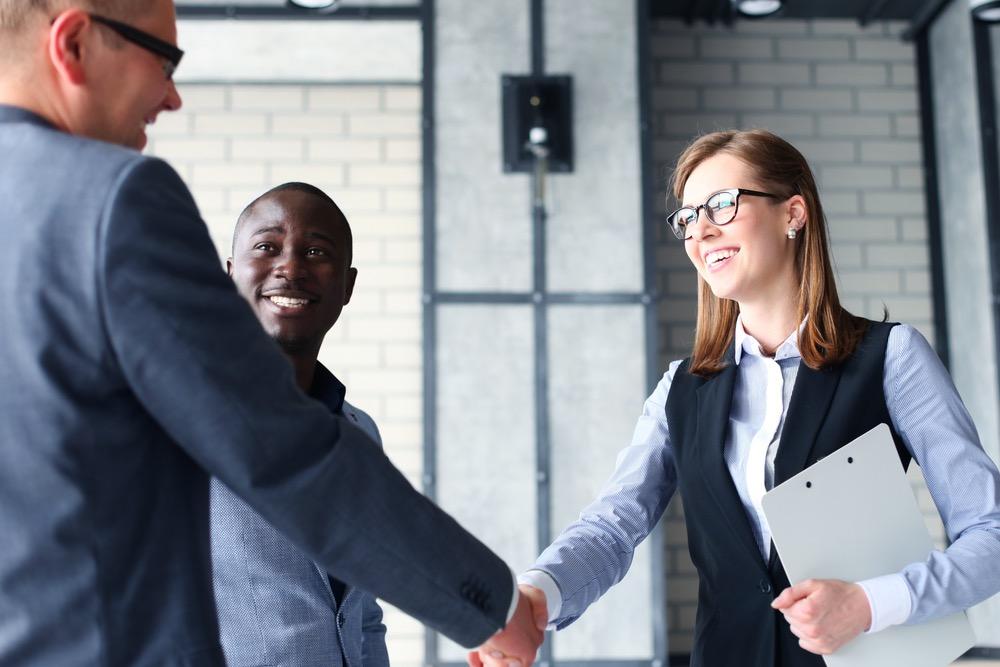 スーツ姿の男性と握手する笑顔の女性