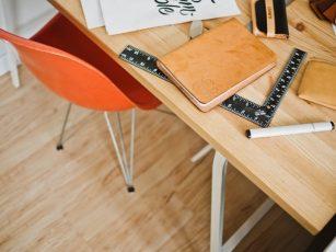 ノートやペン、定規が置かれた机とオレンジ色の椅子