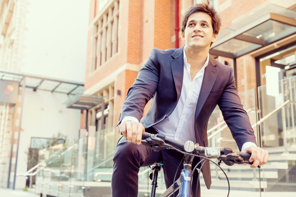 スーツ姿で自転車に乗る男性