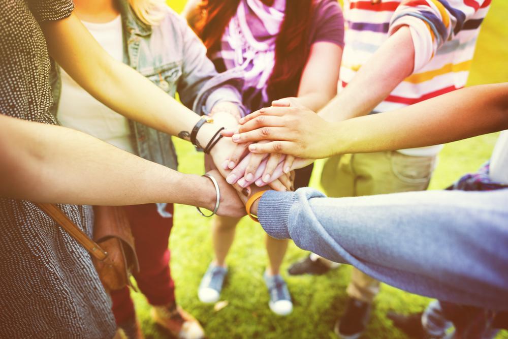 輪になって手を重ね合わせる男女のグループ
