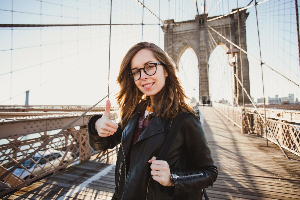 橋の上でサムズアップするメガネをかけた女性
