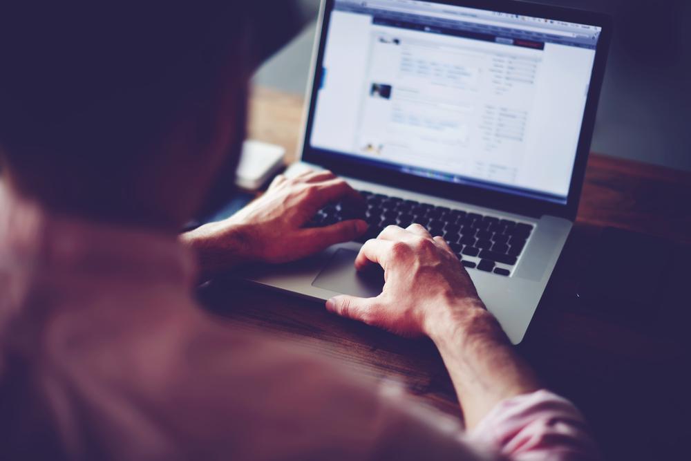 暗い部屋でノートパソコンを操作する男性