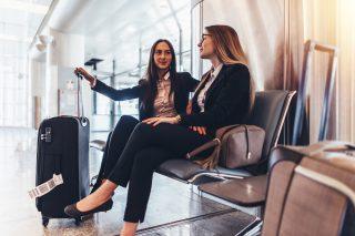 スーツケースを並べ空港の椅子に座る2人の女性