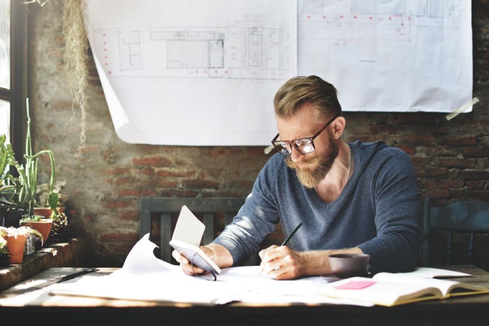 スマートフォンを見ながら設計図を書く男性