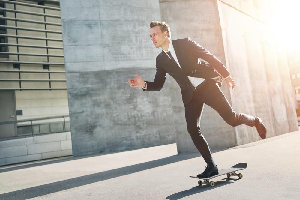 スケートボードに乗って移動するスーツ姿の男性