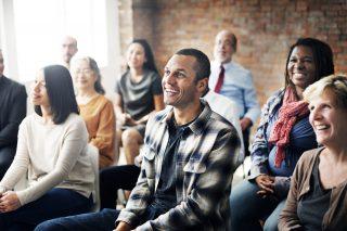 笑顔でセミナーを聞く人々