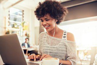 ノートパソコンを見て笑顔になる女性