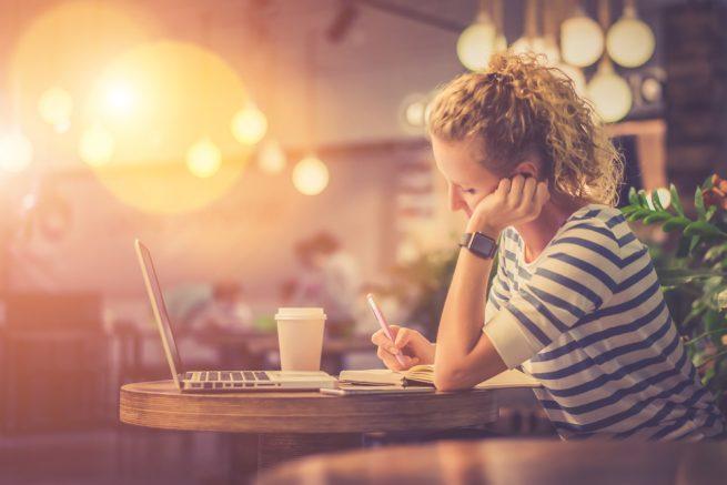 カフェでドリンクを飲みながらノートに何か書き込む女性