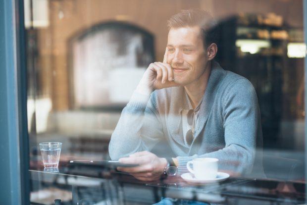 カフェの窓際に座り往来を眺める男性